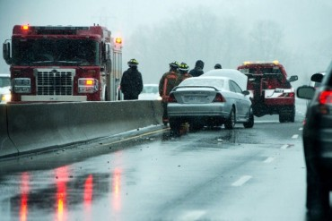 TORONTO, ONTARIO: April 11, 2013 - Firefighters and a tow truck attend to a traffic accident on the Don Valley Parkway on an unseasonably rainy and snowy spring day in Toronto, Ontario, April 11, 2013.  (Tyler Anderson/National Post)  (For Toronto) //NATIONAL POST STAFF PHOTO